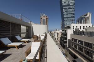 מרפסת הגג הצופה אל העיר ומצויידת בפינות ישיבה ומיטות שיזוף | ניתן לראות גם את הים